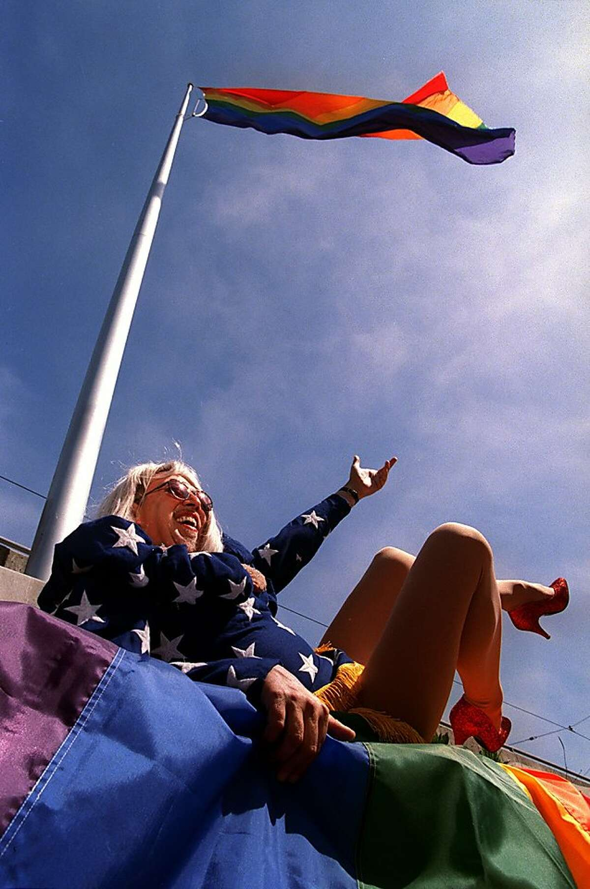 """DRAG/C/23JUN99/MN/RW Gilbert Baker, otherwise known as the """"Gay Betsy Ross,"""" sits under a giant rainbow flag, that symbolizes gay pride, dressed in drag in the Castro neighborhood in San Francisco. BY ROBIN WEINER/THE CHRONICLE."""