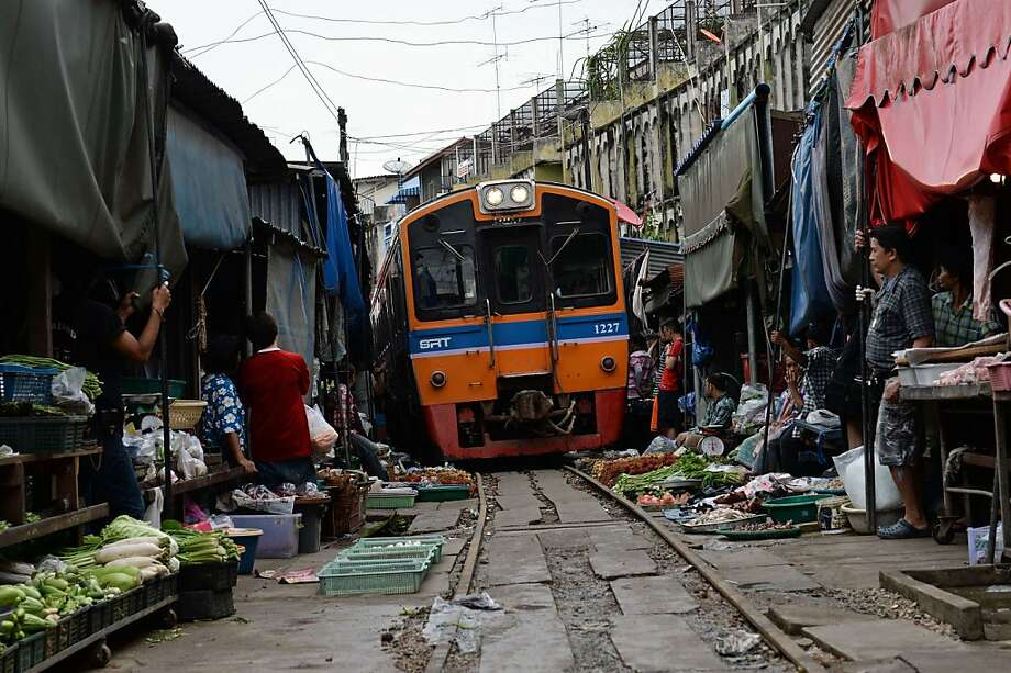 This picture taken on June 25, 2013 shows a train passing through a food market in Maeklong, some 60 kilometers south-west of Bangkok.  Several times a day, shopkeepers swiftly pack up their food stalls and pull back their canopies to let the trains pass. Once the trains have rumbled through, the crates of vegetables, fish and eggs, are heaved back into their position along the tracks and shoppers return to the tracks they use as a path through the market. Every day hundreds of tourists armed with cameras flock to the picturesque Maeklong market to witness the well-oiled routine.   AFP PHOTO/Christophe ARCHAMBAULTCHRISTOPHE ARCHAMBAULT/AFP/Getty Images Photo: Christophe Archambault, AFP/Getty Images