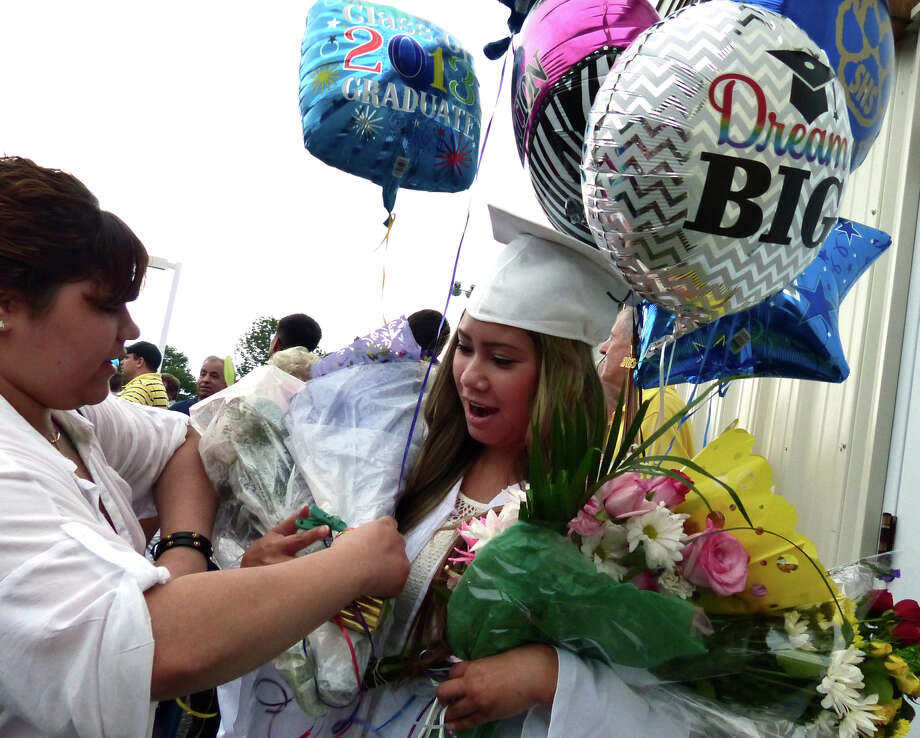 Graduate Sara Somsanouk is given flowers to hold by her cousin Megan Hernandez so a photo can be taken after Seymour High School's 126th Annual Commencement in Seymour, Conn. on Thursday June 27, 2013. Photo: Christian Abraham / Connecticut Post