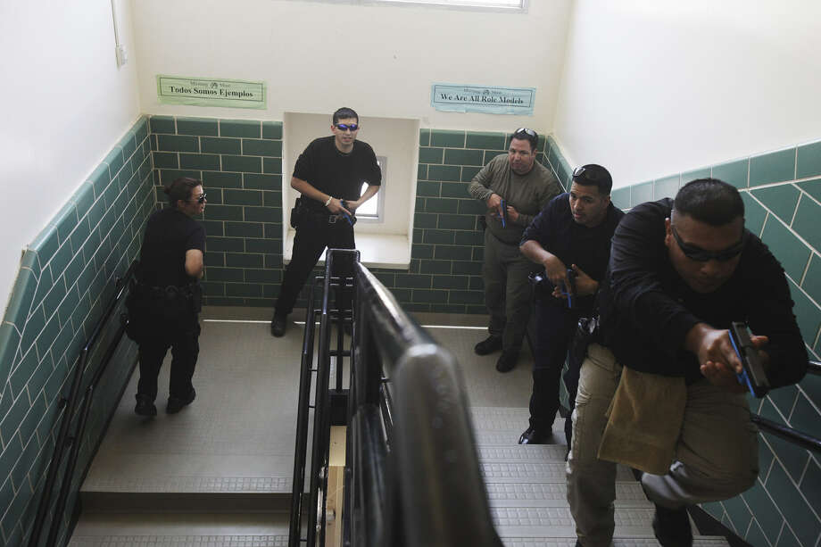 Edgewood officers practice climbing stairs during the training. Students in Kennedy High School's criminal justice academy helped the officers act out emergencies. The training was made possible by the Alamo Area Council of Governments.