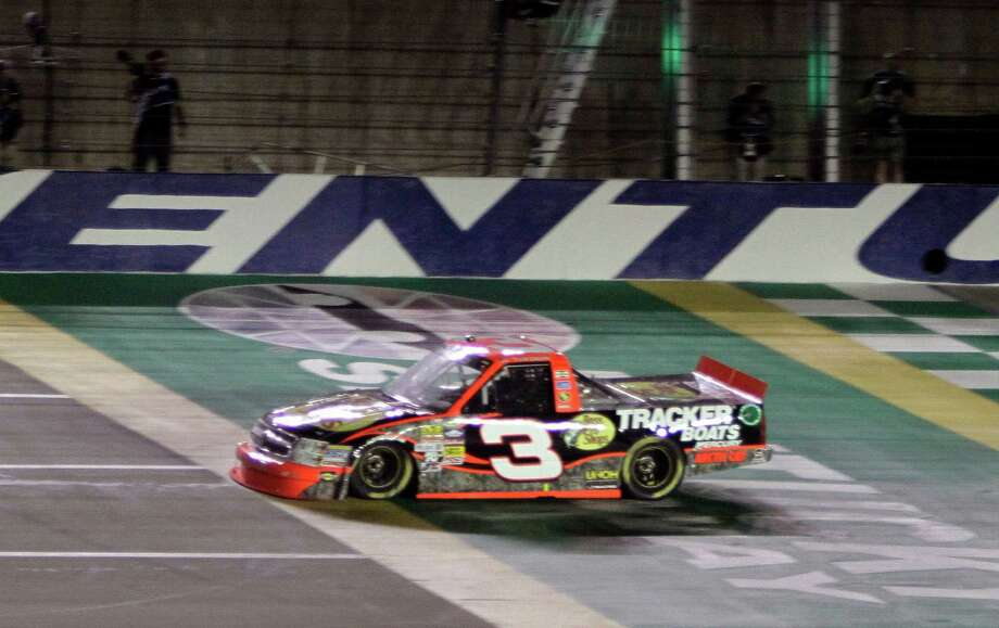 Ty Dillon crosses the finish line to win the NASCAR Truck Series auto race at Kentucky Speedway in Sparta, Ky., Thursday, June 27, 2013. (AP Photo/Garry Jones) ORG XMIT: KYGJ117 Photo: Garry Jones / FR50389 AP
