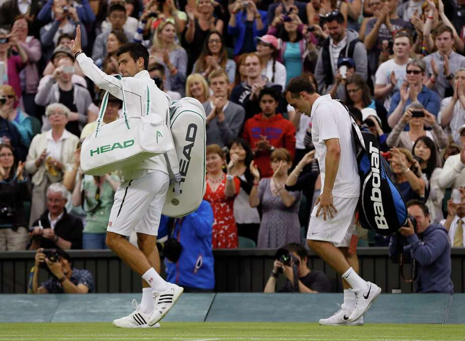 Novak Djokovic of Serbia, left, waves to spectators after defeating Bobby Reynolds of the United States in their Men's second round singles match as they walk off the court at the All England Lawn Tennis Championships in Wimbledon, London, Thursday, June 27, 2013. (AP Photo/Kirsty Wigglesworth)  ORG XMIT: WIM405 Photo: Kirsty Wigglesworth / AP