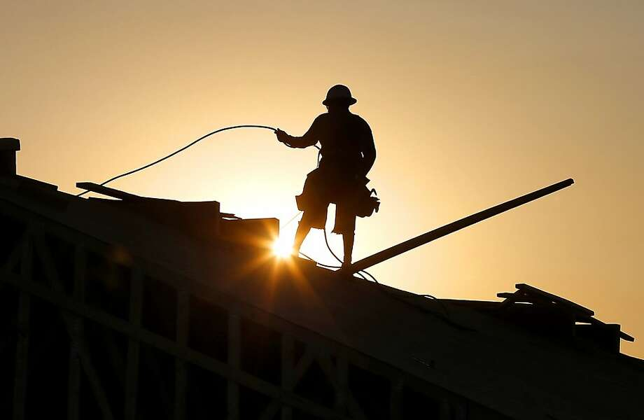 A construction worker is shown atop a roof at sunrise to beat daytime high temperatures, Thursday, June 27, 2013 in Queen Creek, Ariz. Excessive heat warnings will continue for much of the Desert Southwest as building high pressure triggers major warming in eastern California, Nevada, and Arizona. Dangerously hot temperatures are expected across the Arizona deserts throughout the week with a high of 118 by Friday. (AP Photo/Matt York) Photo: Matt York, Associated Press
