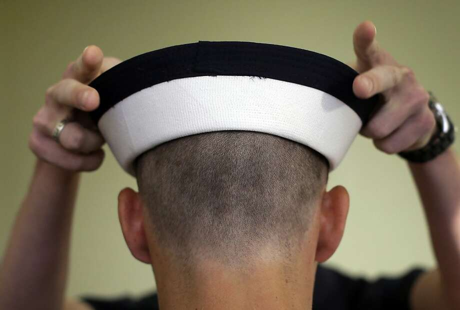 "A prospective plebe is fitted for a U.S. Navy cover during Induction Day at the U.S. Naval Academy, Thursday, June 27, 2013, in Annapolis, Md. More than 1,200 men and women reported for ""I-Day,"" the first day of Plebe Summer, where they received haircuts, new uniforms and instructions on how to salute before taking an oath of office to become members of the Class of 2017. (AP Photo/Patrick Semansky) Photo: Patrick Semansky, Associated Press"