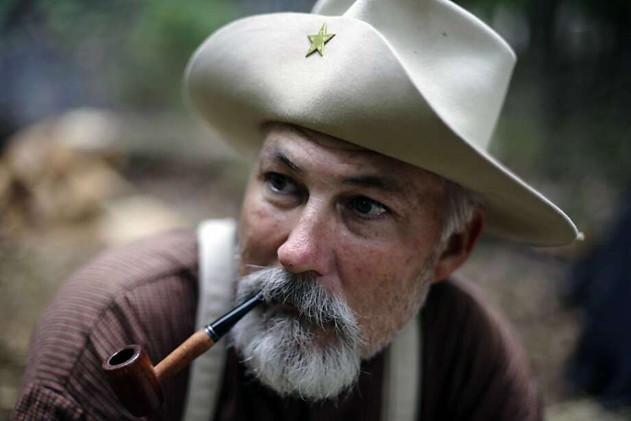 Mike Wilkinson, of San Antonio, portraying a soldier with the 4th Texas Infantry, smokes a pipe during ongoing activities commemorating the 150th anniversary of the Battle of Gettysburg, Thursday, June 27, 2013, in Gettysburg, Pa. Union forces turned away a Confederate advance in the pivotal battle of the Civil War fought July 1-3, 1863, which was also the war's bloodiest conflict with more than 51,000 casualties. (AP Photo/Matt Rourke) Photo: Matt Rourke, Associated Press
