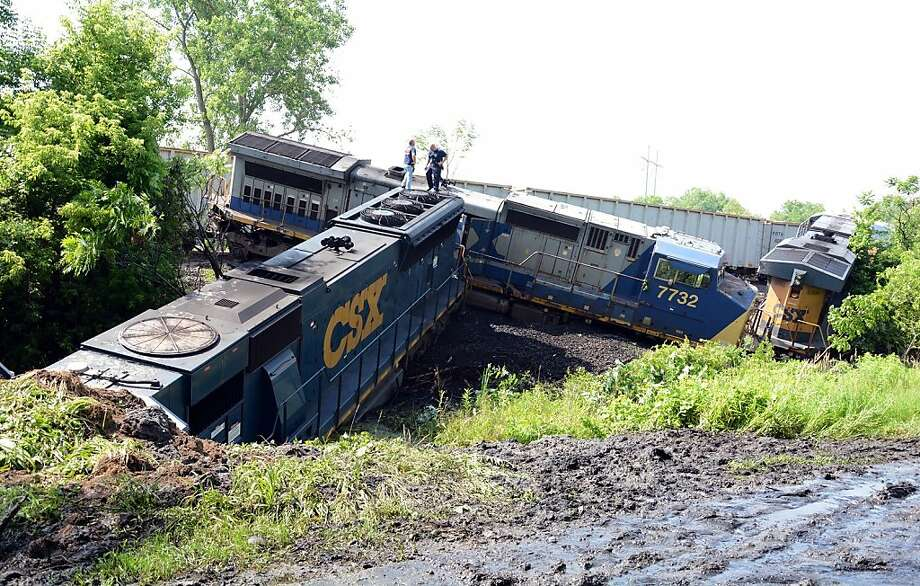 Workmen look over the scene of a train derailment after the collision of two CSX freight trains in the Town of Mohawk, N.Y., a mile west of Fonda, Thursday, June 27, 2013. Amtrak passenger service has been suspended between Albany and Syracuse and a stretch of highway has been closed after about 30 freight train cars derailed in Montgomery County, some of them toppling over. (AP Photo/The Daily Gazette, Marc Schultz) Photo: Marc Schultz, Associated Press