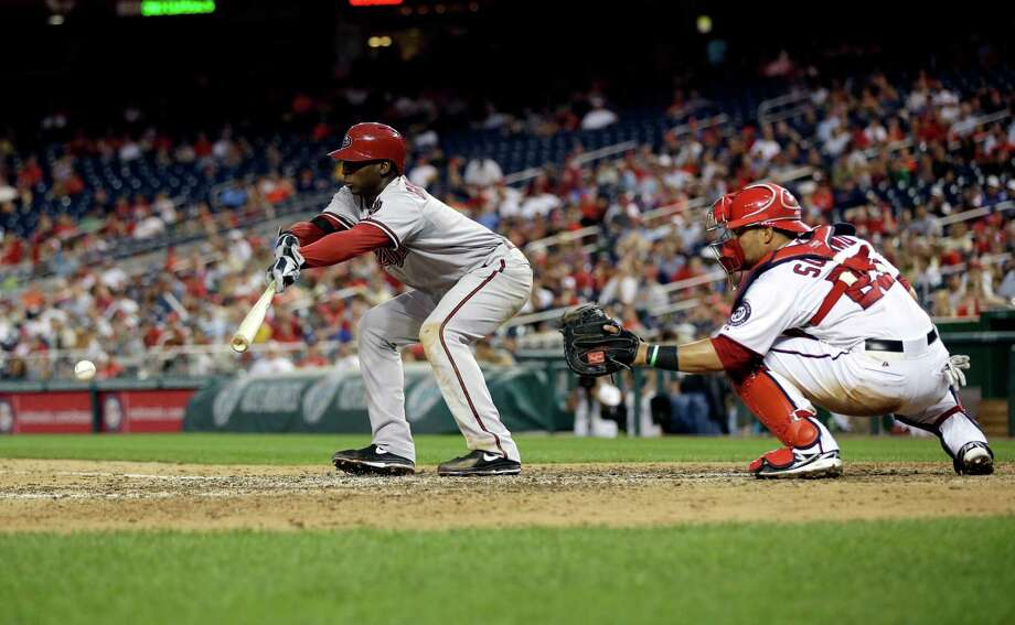 Arizona's Didi Gregorius, left, uses a dose of small ball to plate the winning run with a bunt single in the top of the 11th inning of Thursday's victory over the Nationals. Photo: Pablo Martinez Monsivais, STF / AP