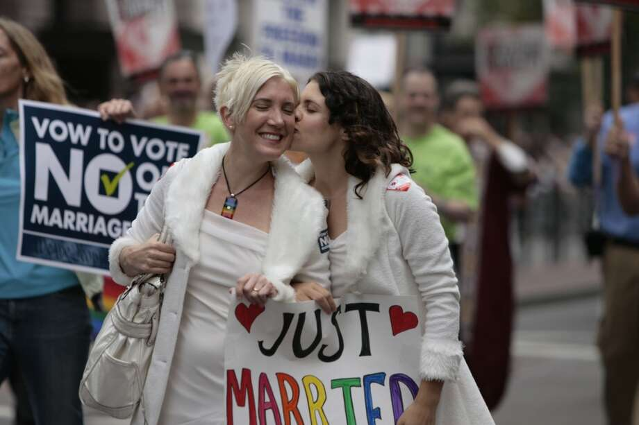 A newlywed couple kiss while walking in the parade during the 38th annual San Francisco Pride weekend.