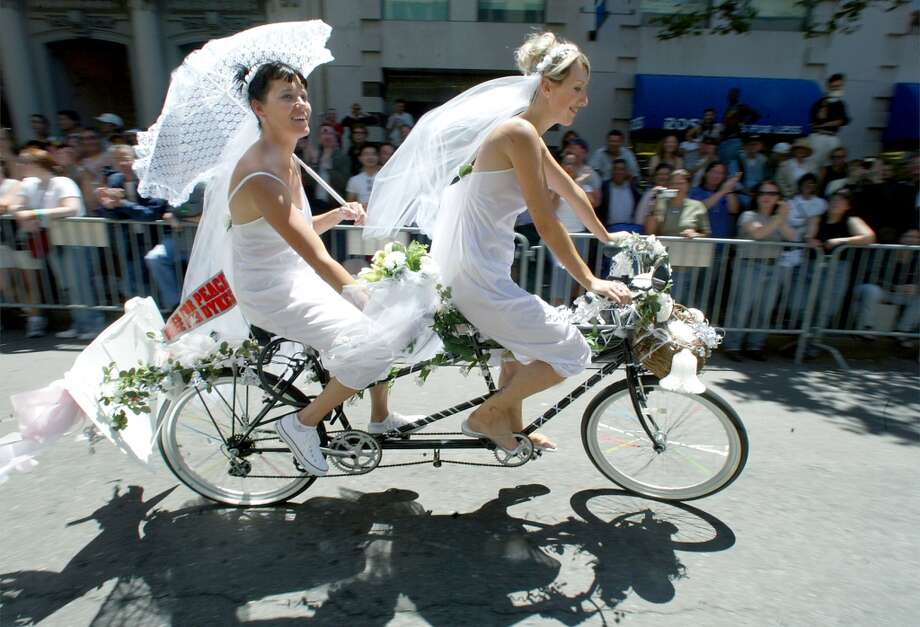 A newly married couple from Sacramento ride their tandem bike at the Pride Parade in San Francisco in 2002.