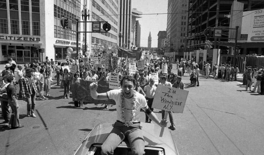 June 25, 1978:  Supervisor Harvey Milk with the Ferry Building in the background during the Gay Freedom Day Parade in 1978.