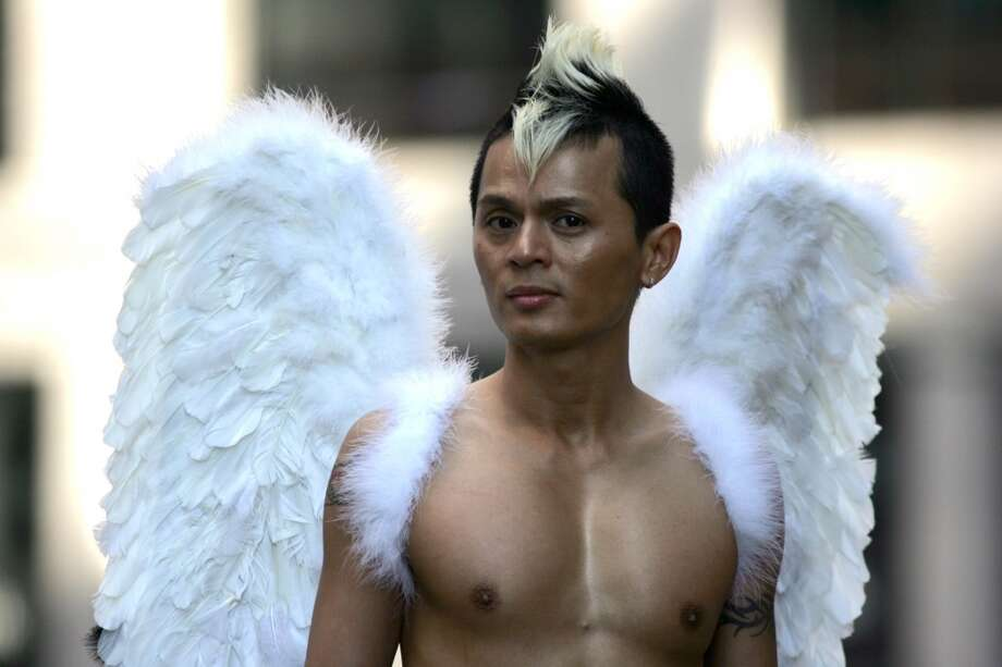 Adorned with angel wings, Leon Ho of the Vietnamese Gay Alliance strolls up Fremont Street before the 2009 Pride Parade in San Francisco.