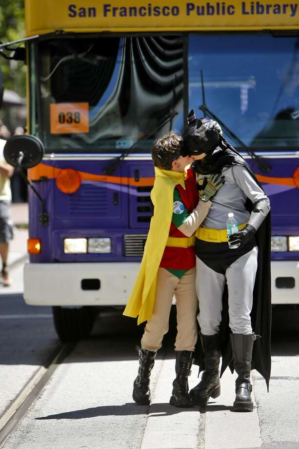 Huckleberry Greenlee, left, kisses Jennifer Collins dressed as Robin and Batman as they march with the San Francisco Public Library in the 40th annual Gay Pride Parade in San Francisco.