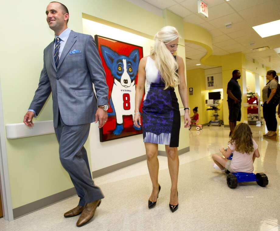 Houston Texans quarterback Matt Schaub and his wife, Laurie, walk through the halls as Summer Davis rides past on a tricycle at Texas Children's Hospital West Campus Thursday, June 27, 2013, in Houston. The Schaubs announced during a news conference a $250,000 donation for emergency center expansion. The donation comes through the Gr8Hope Foundation. ( Brett Coomer / Houston Chronicle )