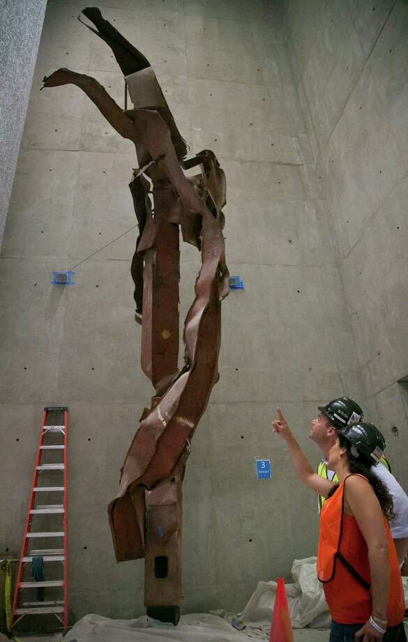Joe Daniels, left, 911 Memorial President, and Anthoula Katsimatides, a member of the 911 Memorial board, discuss a twisted steel column from the World Trade Center (WTC) site, installed at the 911 Memorial Museum on Thursday, June 27, 2013 in New York.  Recovered from the WTC site after September 11, 2001, this column once stood in the core of the South Tower.  (AP Photo/Bebeto Matthews) ORG XMIT: NYBM105 Photo: Bebeto Matthews, AP / AP