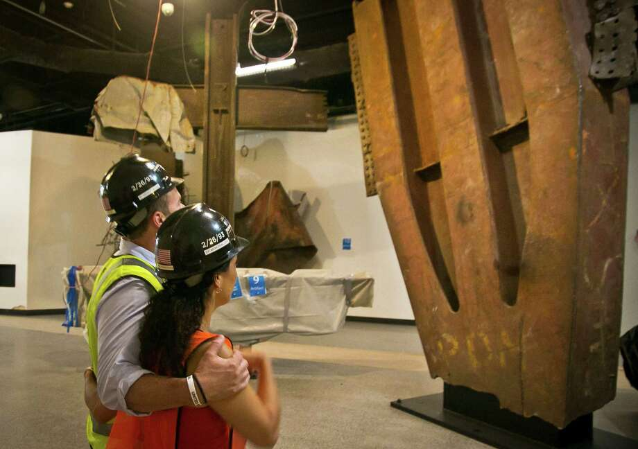 Joe Daniels, left, 911 Memorial President, comforts Anthoula Katsimatides, left, a member of the 911 Memorial board, as they view installations, including a steel cross beam, center, recovered from the World Trade Center (WTC) site and installed at the 911 Memorial Museum, Thursday, June 27, 2013 in New York.  The 17-foot-tall intersecting steel column and crossbeam was found in the rubble of 6 World Trade Center on September 13, 2001.  It has since been perceived as a religious symbol by many, receiving an official ceremonial blessing of the cross.  (AP Photo/Bebeto Matthews) ORG XMIT: NYBM106 Photo: Bebeto Matthews, AP / AP