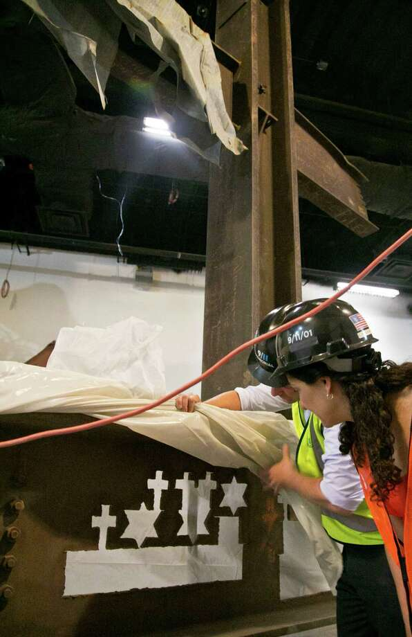 Joe Daniels, left, 911 Memorial President, and Anthoula Katsimatides, left, a member of the 911 Memorial board, lift a cover to reveal symbol cutouts in a steel column recovered from the World Trade Center (WTC) site, during a tour of the 911 Memorial Museum,  Thursday, June 27, 2013 in New York.    Recovered from the World Trade Center after September 11, 2001, some ironworkers cut symbols and shapes out of discarded steel during their breaks to give as mementos and tokens of comfort to other workers and victims' relatives.  (AP Photo/Bebeto Matthews) ORG XMIT: NYBM114 Photo: Bebeto Matthews, AP / AP