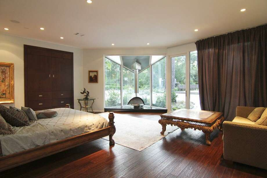 Master bedroom w/ dark stained hardwood floors & custom gas log fireplace.