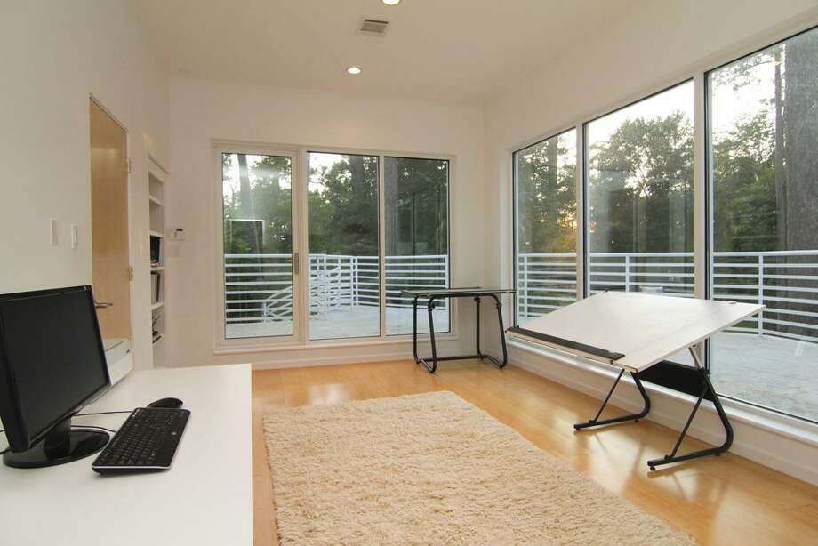 Upstairs office or art room has abundant natural light. Access door leading to balcony w/ pool and backyard views.
