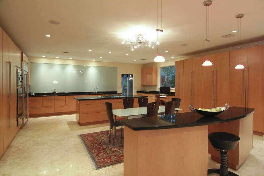 Contemporary hanging light fixtures above secondary kitchen island.