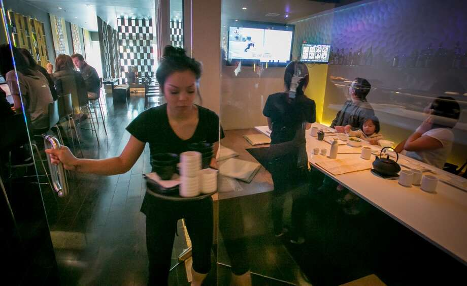 A server brings tea into a glassed Karaoke room.