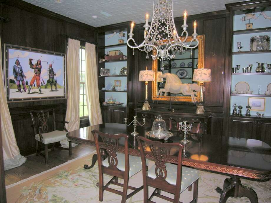 MAIN HOUSE - Dining Room with mahogany wood paneling and walls of bookshelves, wood floor, crown molding, custom embossed tin ceiling, and recessed lighting and chandelier.
