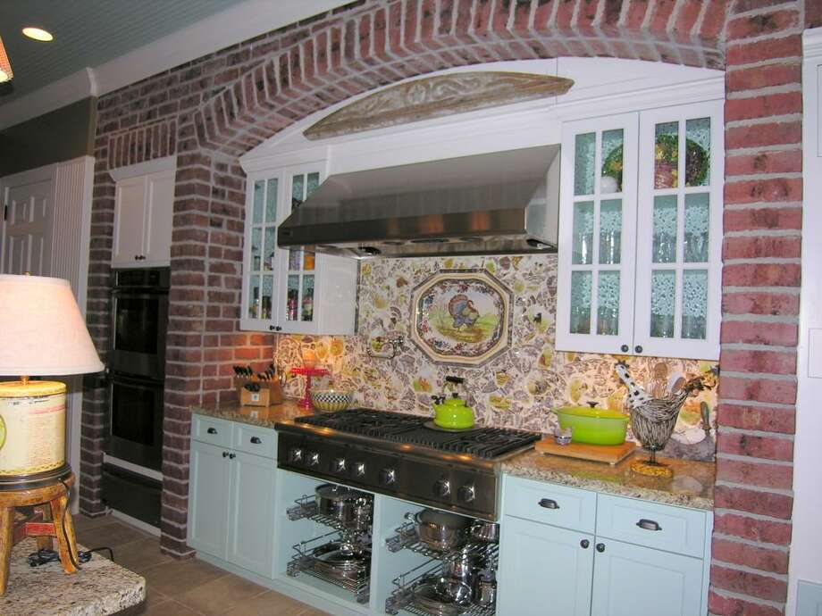 MAIN HOUSE KITCHEN - Custom back splash from Spode and antique plates, beadboard walls & ceiling, wall mount flat screen TV, Stainless fixtures by Water Works, antique hardware,Tidings apron sink by Kohler, travertine floor with marble insert border.