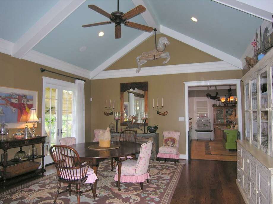 Great Room looking back toward kitchen with casual dining area, high-pitched beamed ceiling, French doors across back to large veranda, hardwood floors.