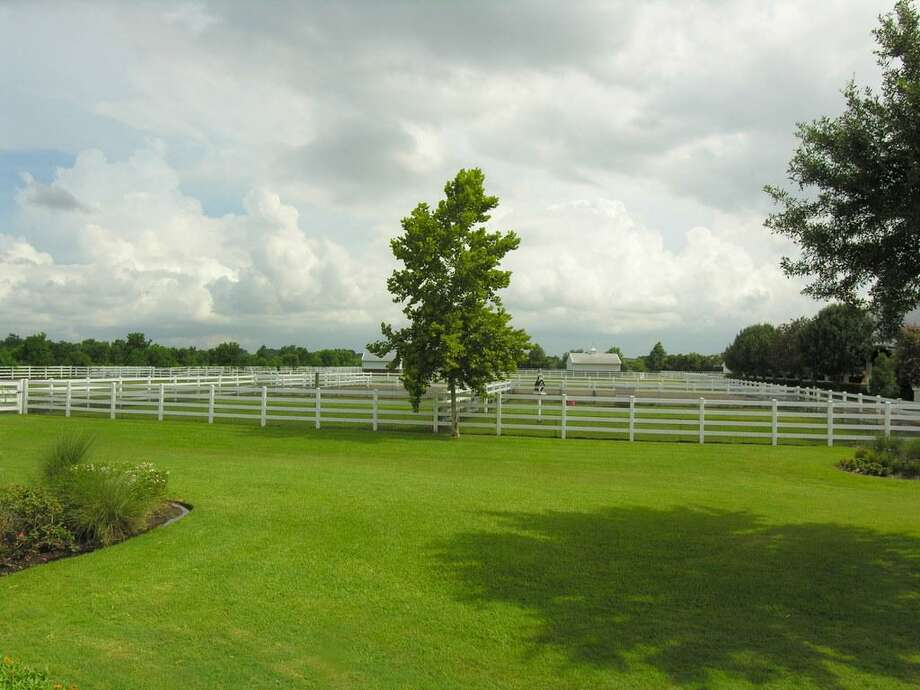 Back yard - NOW with a large outdoor riding arena beyond the fence has a clay base with bank sand top. There is flexiboard around exterior and hidden water sprinklers to keep surface perfect for riding Western or English style. Horse jumps here, too.
