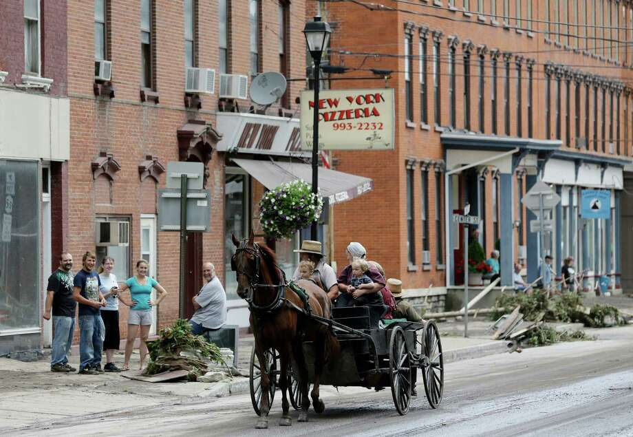 An Amish cart rides along Main Street after flooding on Friday, June 28, 2013, in Fort Plain, N.Y.  Severe flooding caused by the spring and early summer's persistent rains damaged houses, closed roads and forced people to flee their homes Friday in New York's Mohawk Valley. Heavy rains Thursday and into early Friday caused the Mohawk River to overflow it banks where it traverses the southern end of Herkimer County, located 60 miles east of Syracuse.  (AP Photo/Mike Groll) ORG XMIT: NYMG105 Photo: Mike Groll, AP / AP