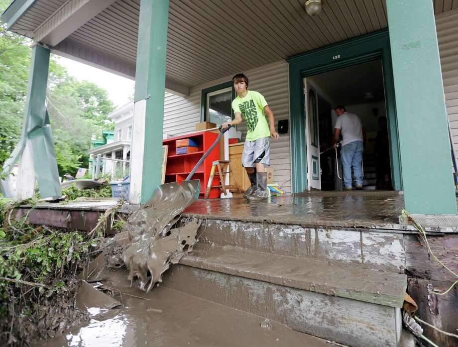 Brendan Hazzard shovels mud from a friend's flood-damaged home on Friday, June 28, 2013, in Fort Plain, N.Y.  Severe flooding caused by the spring and early summer's persistent rains damaged houses, closed roads and forced people to flee their homes Friday in New York's Mohawk Valley. Heavy rains Thursday and into early Friday caused the Mohawk River to overflow it banks where it traverses the southern end of Herkimer County, located 60 miles east of Syracuse.  (AP Photo/Mike Groll) ORG XMIT: NYMG101 Photo: Mike Groll, AP / AP