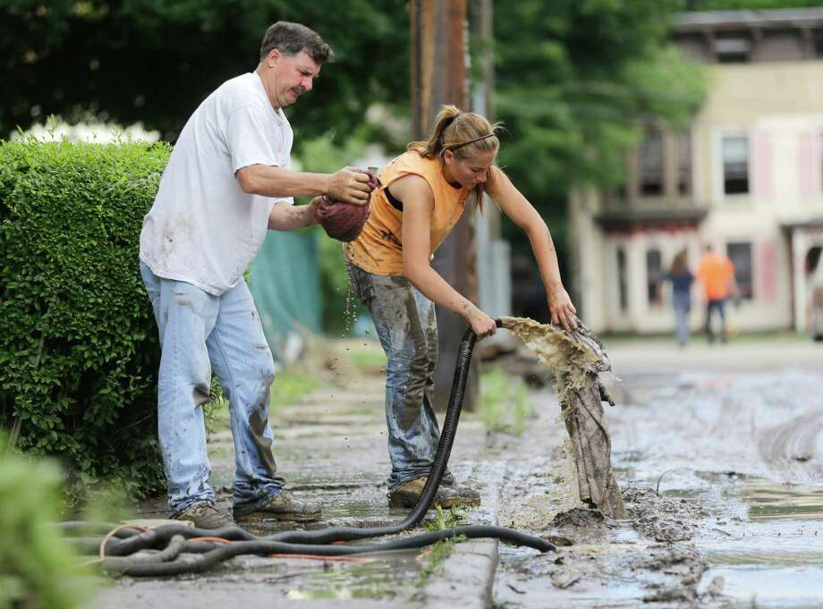 Rodney Young, left, and Lesly Hazzard hose off towels they're using to clean mud from a flood-damage house that Young owns on Friday, June 28, 2013, in Fort Plain, N.Y.  Severe flooding caused by the spring and early summer's persistent rains damaged houses, closed roads and forced people to flee their homes Friday in New York's Mohawk Valley. Heavy rains Thursday and into early Friday caused the Mohawk River to overflow it banks where it traverses the southern end of Herkimer County, located 60 miles east of Syracuse.  (AP Photo/Mike Groll) ORG XMIT: NYMG102 Photo: Mike Groll, AP / AP