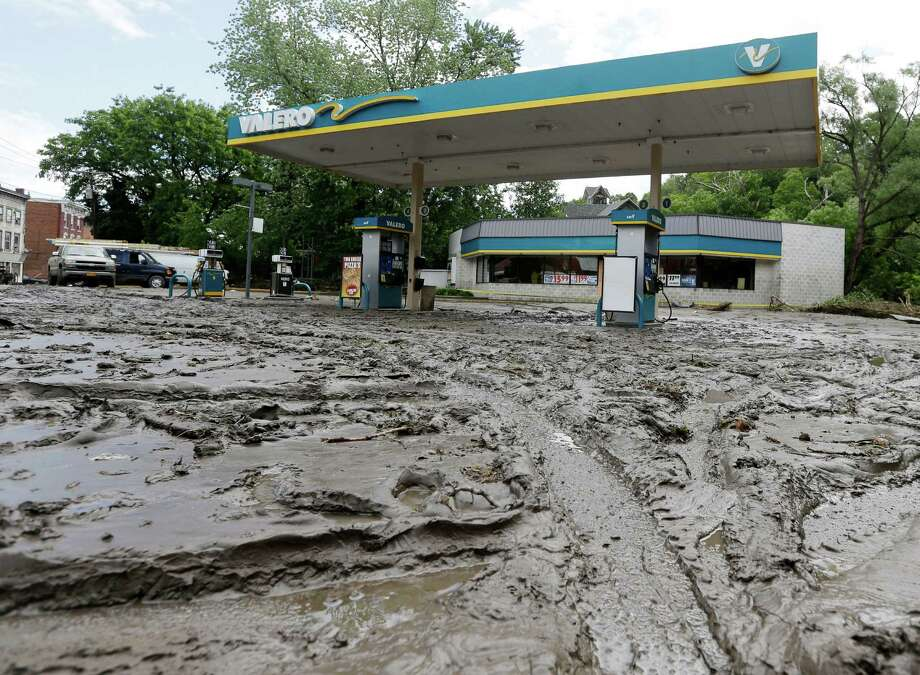 Mud fills the parking lot of a convenience store after flooding on Friday, June 28, 2013, in Fort Plain, N.Y.  Severe flooding caused by the spring and early summer's persistent rains damaged houses, closed roads and forced people to flee their homes Friday in New York's Mohawk Valley. Heavy rains Thursday and into early Friday caused the Mohawk River to overflow it banks where it traverses the southern end of Herkimer County, located 60 miles east of Syracuse.  (AP Photo/Mike Groll) ORG XMIT: NYMG103 Photo: Mike Groll, AP / AP