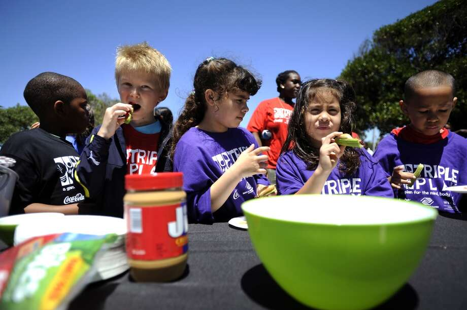 Children work on making 'snails' with celery, apples, raisins and peanut butter during the Boys & Girls Club Triple Play event held on Treasure Island Thursday. June 27th to celebrate National Fruit and Vegetable Month.