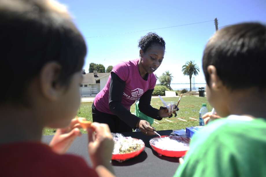 Olympian Gail Devers (center) and the children put together cups of fresh salsa at the Salsa Table.