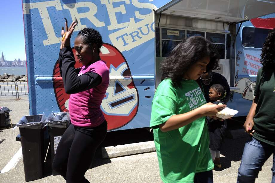 Olympian Gail Devers dances next to a taco truck as kids snack on veggie tacos.