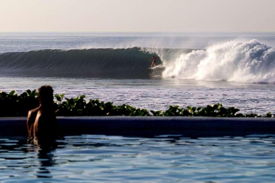 Taj Burrow of Australia surfs as a spectator watches from the pool on June 25, 2013 in Denpasar, Bali, Indonesia.