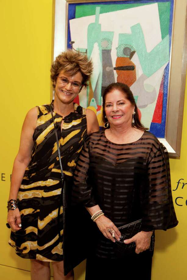 "Museum of Fine Arts, Houston curator Mari Carmen Ramirez, left, and Tanya Capriles de Brillembourg posed in front of Diego Rivera's ""Still Life with Lemons"" before a patron's dinner. Photo: Jenny Antill"