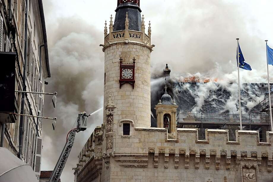 A firefighter douses the burning roof of City Hall in La Rochelle, France. The 15th-century 