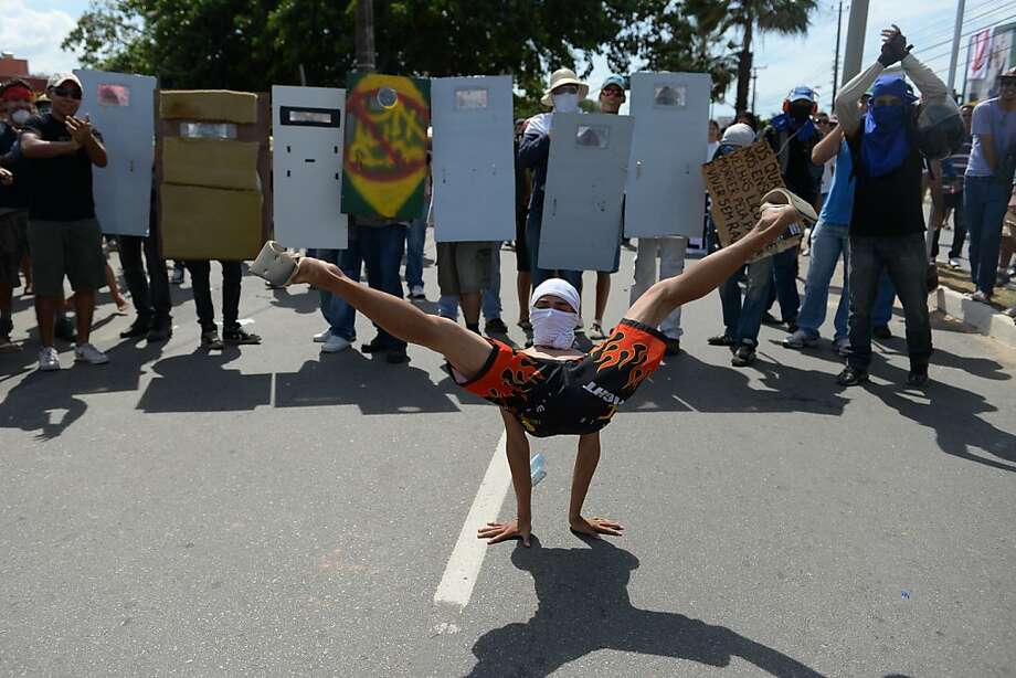 Stop right there and put your hands, er, feet up:In Fortaleza, Brazil, an antigovernment protester marches on a police line (out of frame). Photo: Yasuyoshi Chiba, AFP/Getty Images