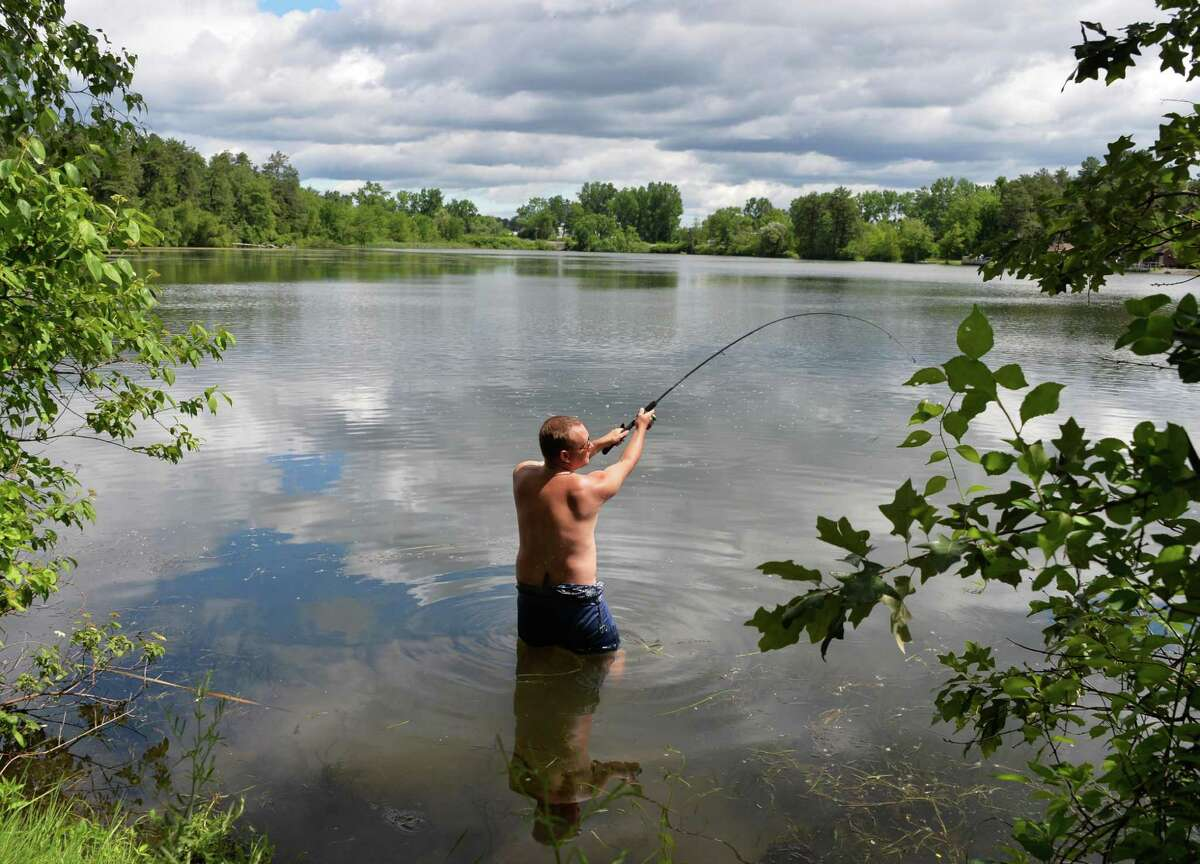 Albany Med student Phil Reid of Plattsburg spends a picture-perfect summer morning casting for bass at Rennselaer Lake at the Pine Bush Preserve in Albany, NY, Friday June 28, 2013. (John Carl D'Annibale / Times Union)