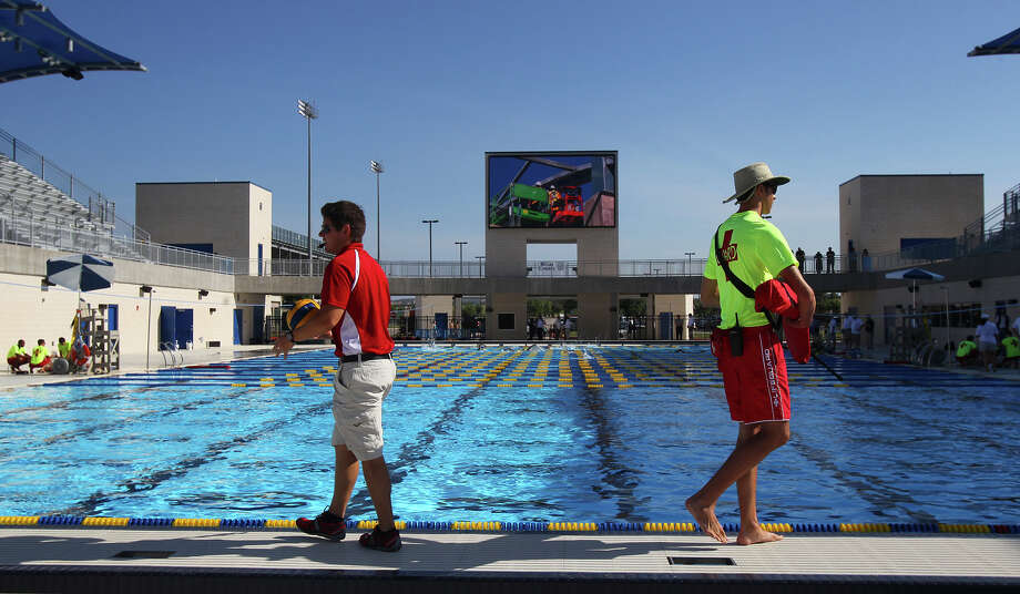 Personnel walk by the water's edge at the new Northside I.S.D. Swim Center before a dedication ceremony held Friday June 28, 2013. The center has three pools, locker rooms, bleachers and more. Photo: JOHN DAVENPORT, SAN ANTONIO EXPRESS-NEWS / ©San Antonio Express-News