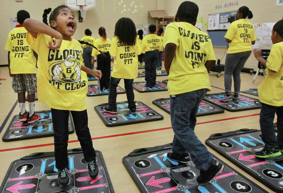 Tyla Mose, 8, exercises with other 3rd grade students as they showcase the new DanceRevolution Classroom Edition video game which will be incorporated into their physical education curriculum at Glover Elementary School on Tuesday, May 7, 2013, in Missouri City.  United Health Care and KONAMI Digital Entertainment, Inc., are joining efforts to reduce childhood obesity in Texas by installing the new DanceDanceRevolution Classroom version.  ( Mayra Beltran / Houston Chronicle ) Photo: Mayra Beltran, Staff / © 2013 Houston Chronicle