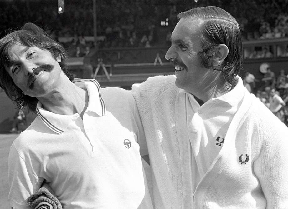 June 1973 — Ilie Nastase (left) of Romania pokes fun at doubles opponent Owen Davidson (Australia) by wearing a false moustache similar to Davidson's prior to their match.