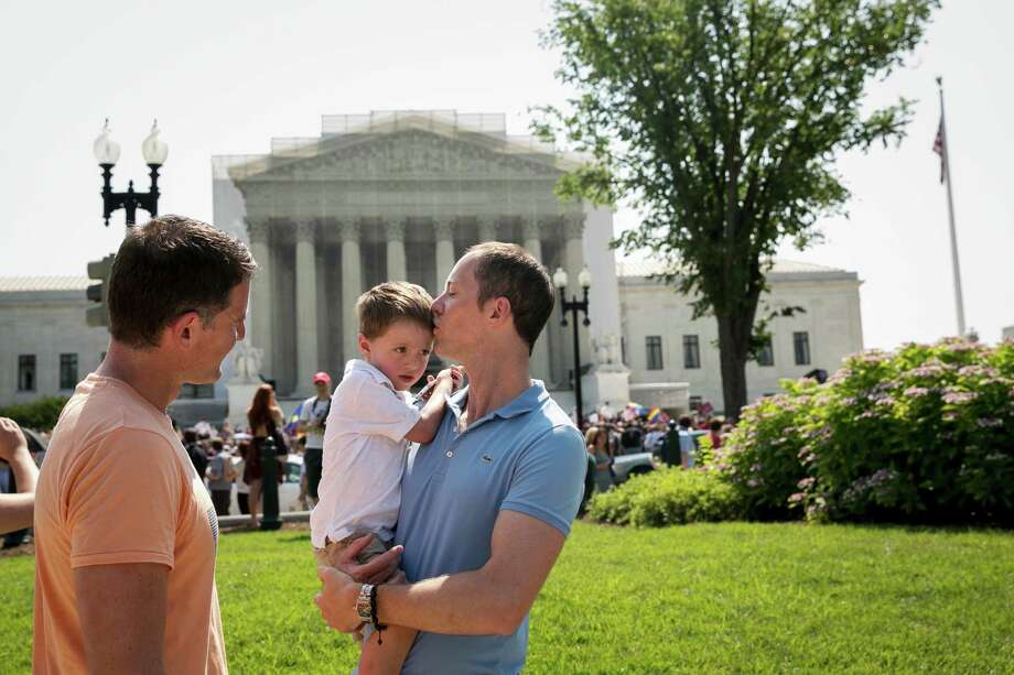 David Huebner, left, and John Barabino, with their son, Miles, outside the Supreme Court, are among the thousands of gay couples for whom states, not the federal government, dictate who is married. Photo: DREW ANGERER, STR / NYTNS