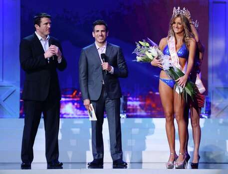 Co-host and mixed martial artist Chael Sonnen, and co-host and former mixed martial artist Kenny Florian look on as Miss Hooters World 2012 Evelise Giorge de Souza of Brazil crowns Kirsten Martins (front) of South Africa Miss Hooters World 2013. Photo: Ethan Miller, Getty Images / 2013 Getty Images