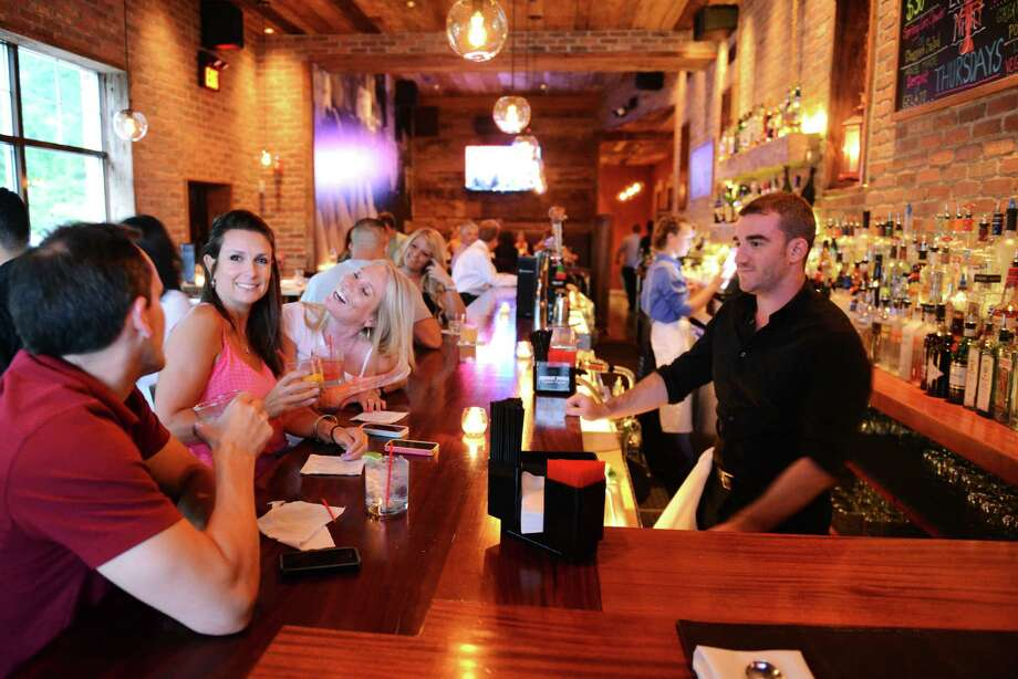 Tom Warlow, left, Jeannine Ludeke, center, and Heidi Brown order drinks from bartender Dave Shepard at Market Place Kitchen & Bar on Mill Plain Road in Danbury, Conn. on Thursday, June 27, 2013.  Mill Plain Road is emerging as the prime Danbury dining district, despite city officials' efforts to revitalize the dining district on Ives Street. Photo: Tyler Sizemore / The News-Times