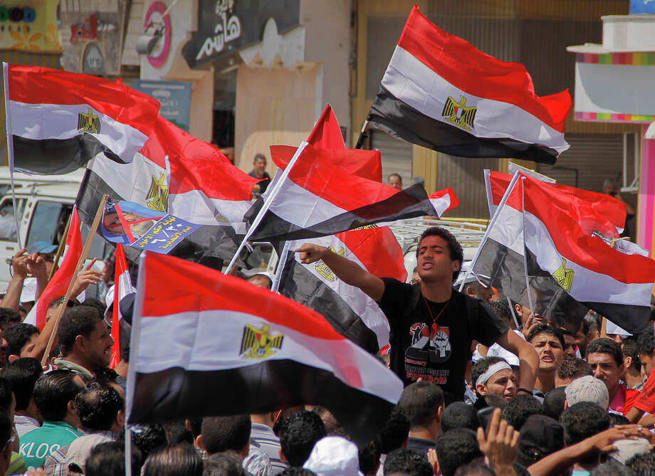 Protesters chant slogans Friday against Egyptian President Mohammed Morsi in downtown Damietta, even as thousands of backers of the Islamist president rallied in Cairo in a show of support. With tensions rising and more opposition demonstrations planned this weekend, foreigners jammed the capital's airport to leave. Photo: Hamada Elrasam, STR / AP