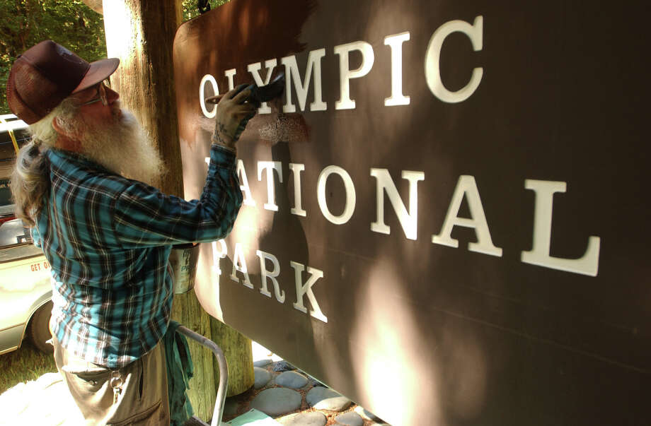 70-year-old John Powell, an Olympic National Park volunteer, repaints the sign near Mora Campground near La Push. Photo: JEFF LARSEN, SEATTLE POST-INTELLIGENCER FILE