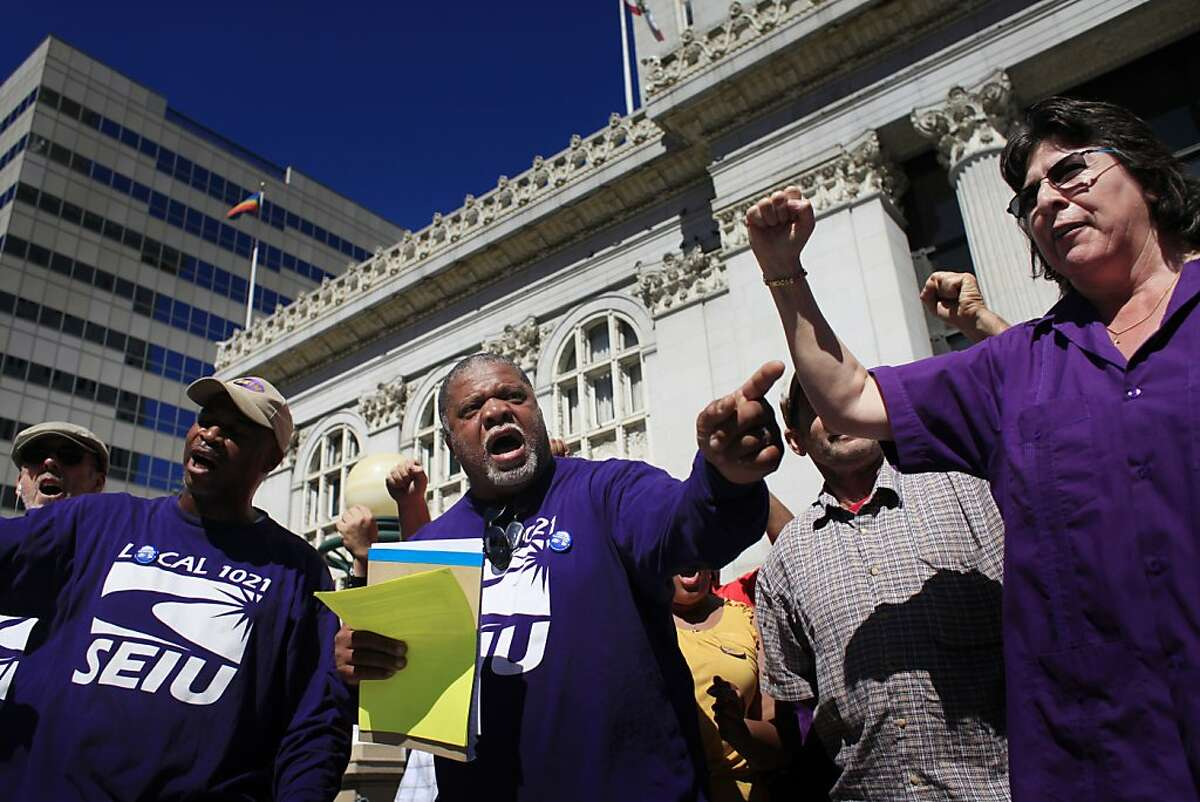 City of Oakland employees Marcus Brown (left) and Dwight McElroy with Roxanne Sanchez, President of SEIU local 1021, yell at the conclusion of a press conference this Friday June 28, 2013 in Oakland, Calif., were BART workers and City of Oakland employees represented by SEIU Local 1021 announced the potential for a mass strike starting on Monday.