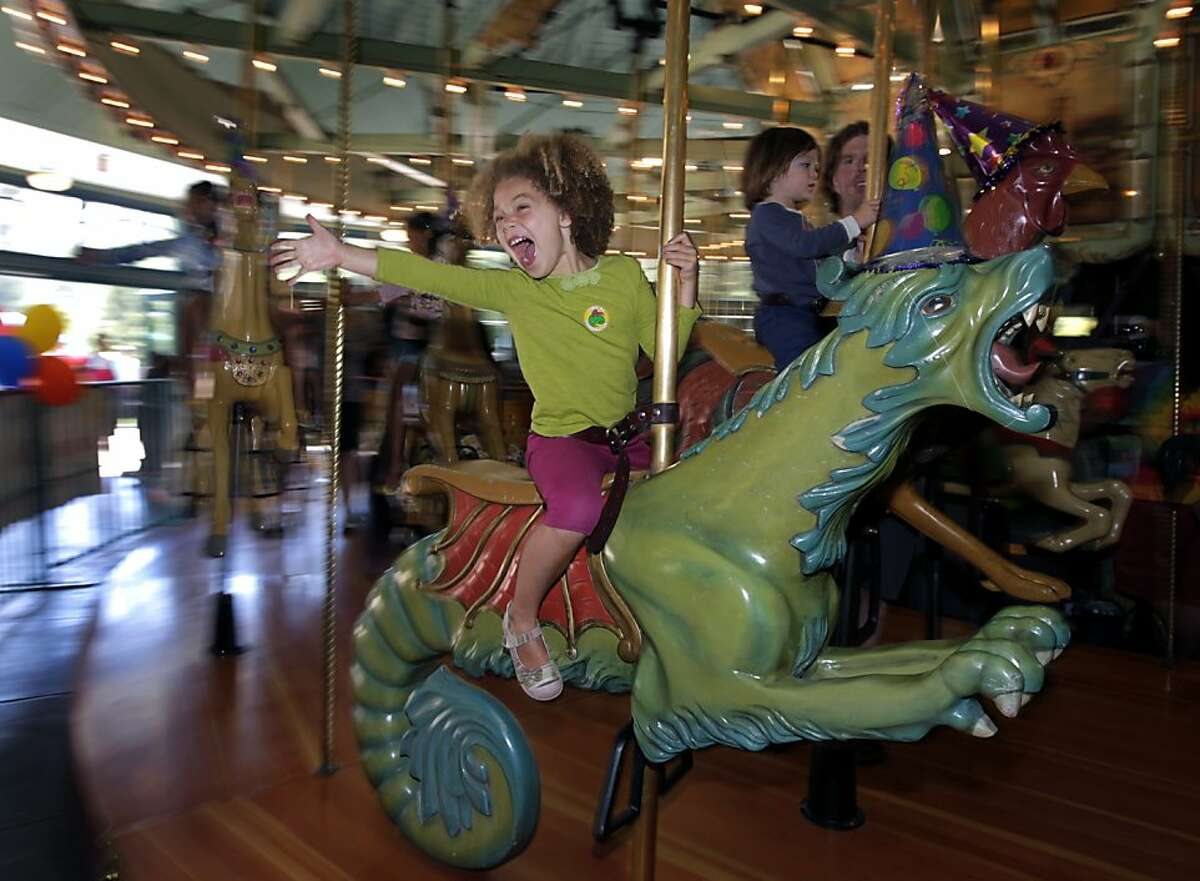 Cecilia Zimmerman, 5, of Oakland, takes a spin on the merry-go-round at Tilden Regional Park during the carousel's 100th birthday celebration in Berkeley, Calif. on Saturday, August 13, 2011. Built by the Herschell-Spillman Company in 1911, the carousel was previously in service in San Bernardino, San Diego and Los Angeles before finding its current home at Tilden Park in 1948.